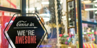 Open sign in the retail store. Bali island. Text come in we are awesome.